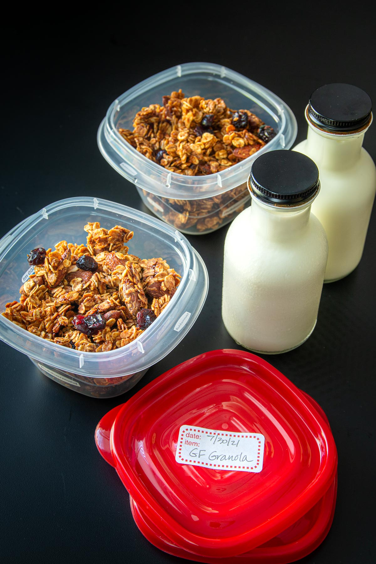 granola in meal prep boxes next to bottles of milk for packing.