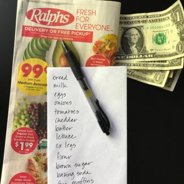 envelope grocery list atop a grocery ad with cash and a pen.