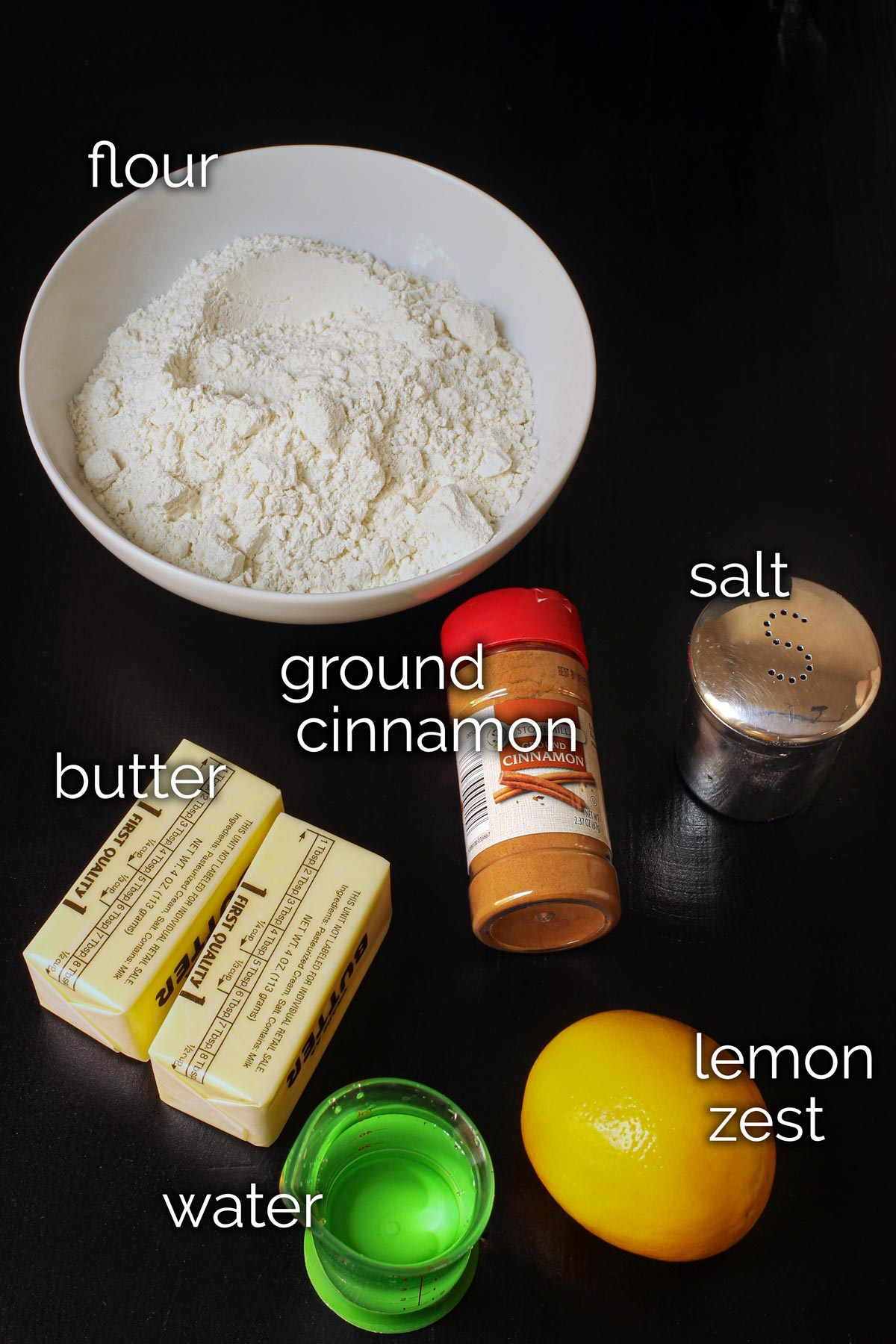 pastry ingredients laid out on black table top.