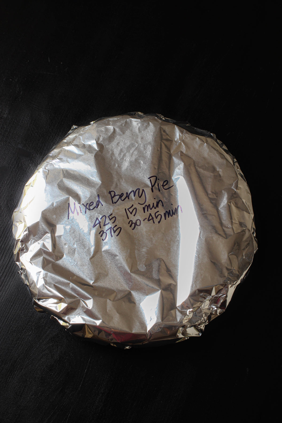 mixed berry pie wrapped with foil and labeled with baking ingredients.