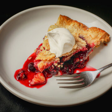white dessert plate with a slice of mixed berry pie and a dollop of whipped cream and a fork.