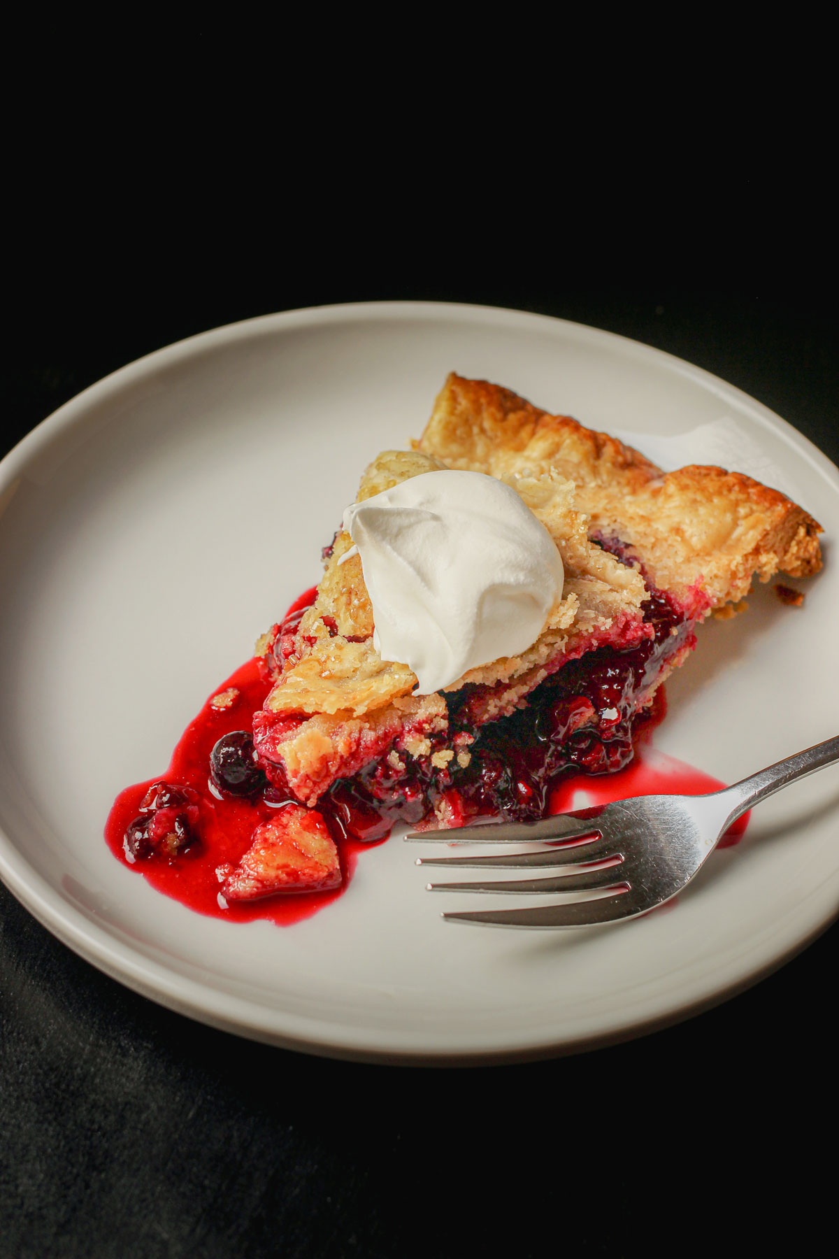 piece of mixed berry pie on a white plate with a fork.
