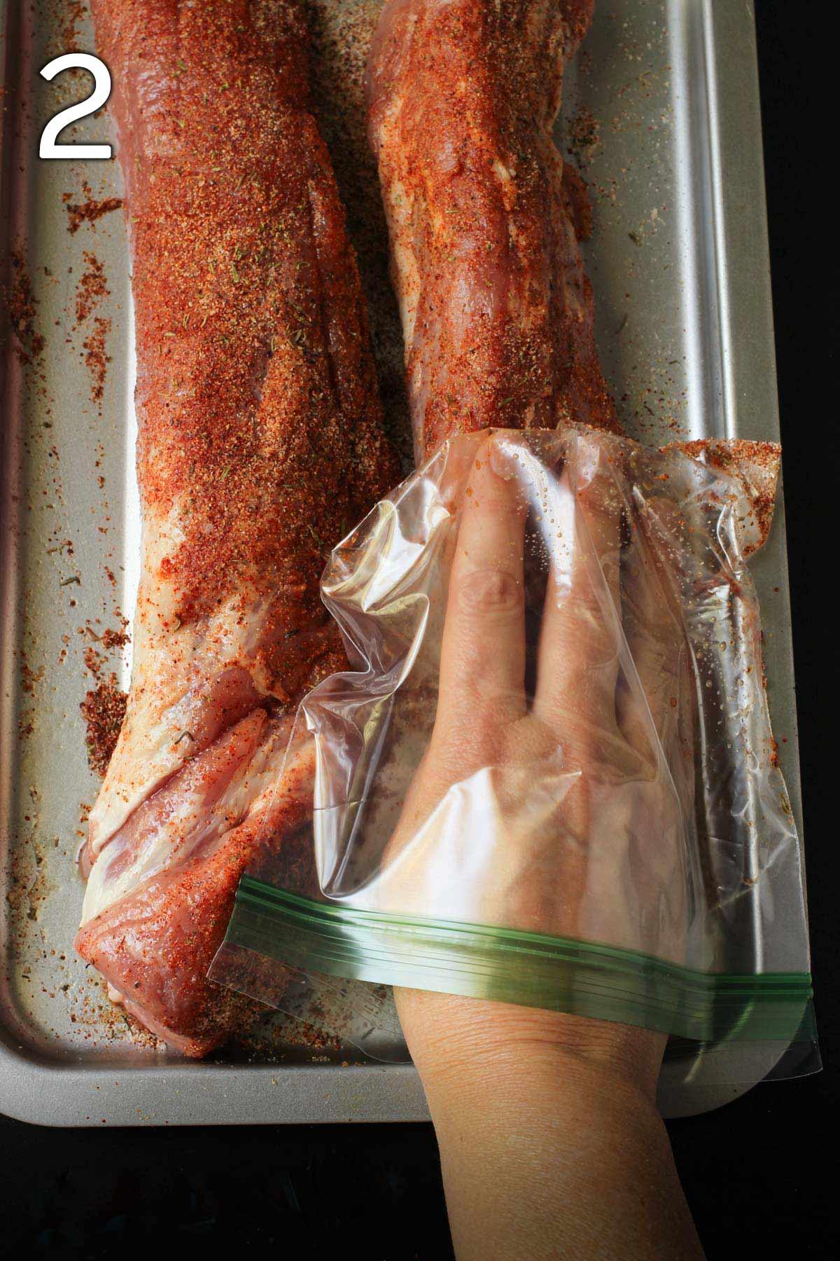 hand in plastic bag rubbing on spice rub.