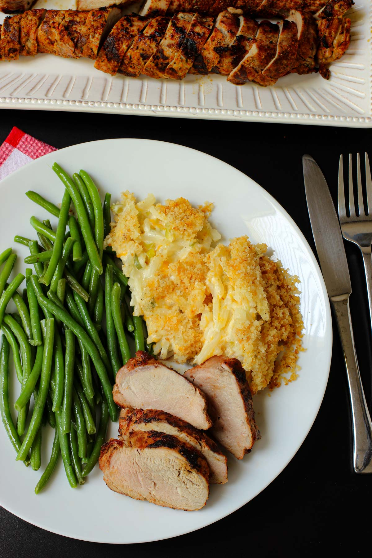 white dinner plate with green beans, hash brown casserole, and grilled pork tenderloin.