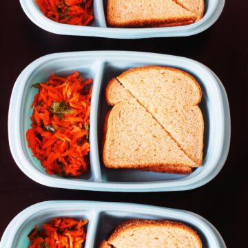 ham and egg salad sandwich packed in teal box with carrot salad.