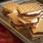 stack of smores on a broiler tray on a red cloth.
