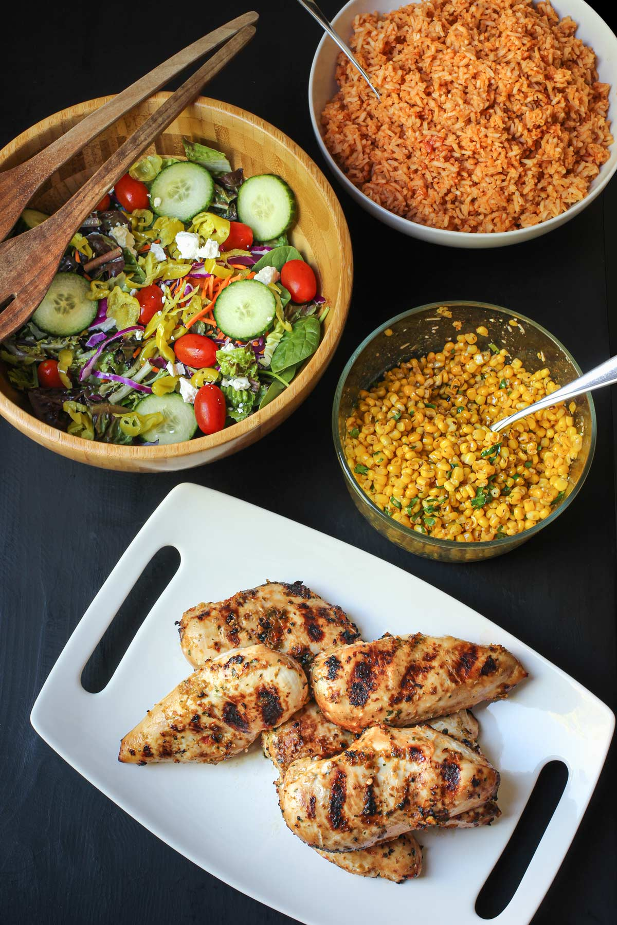 dinner table set with a platter of grilled spicy chicken and bowls of salad, corn, and rice.