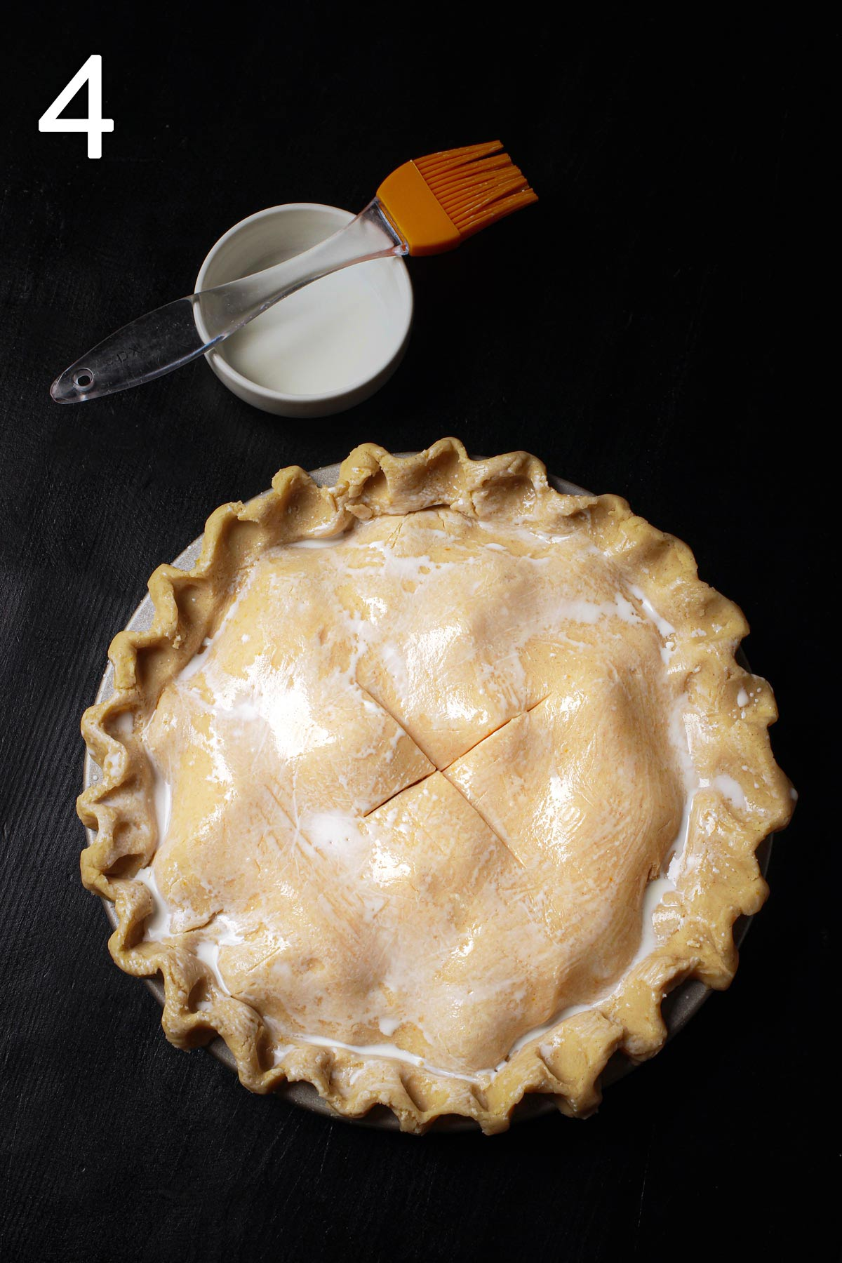 pie brushed with cream next to dish and pastry brush.