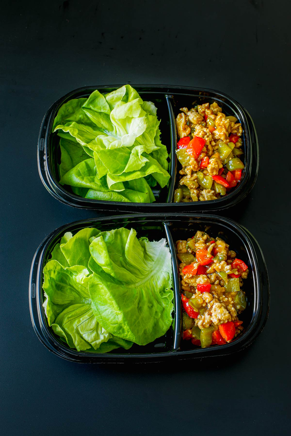 two divided meal prep boxes with lettuce leaves on one side and filling in the other.