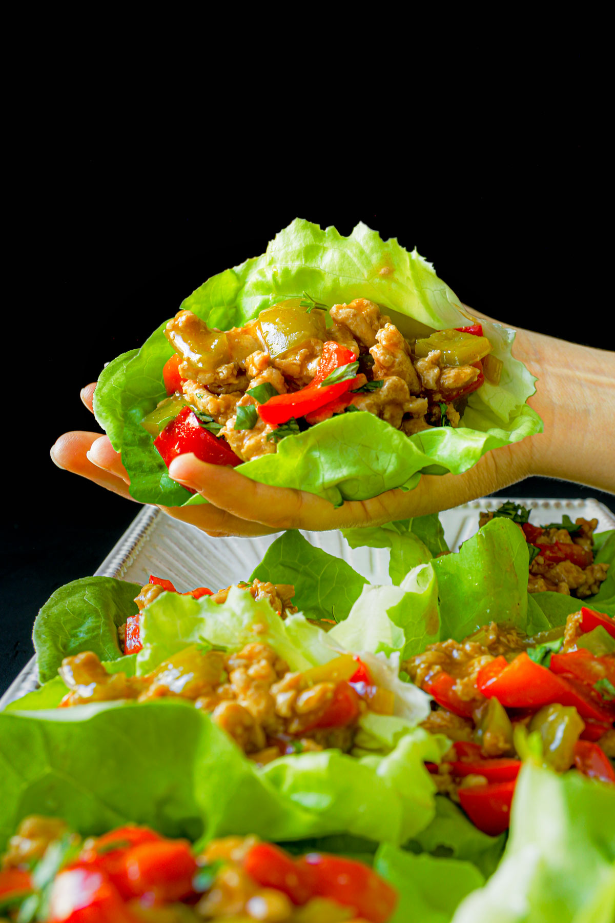 hand holding a turkey lettuce wrap over a platter of wraps.