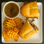 cut french dip sandwich on square plate with cup of jus and waffle fries.