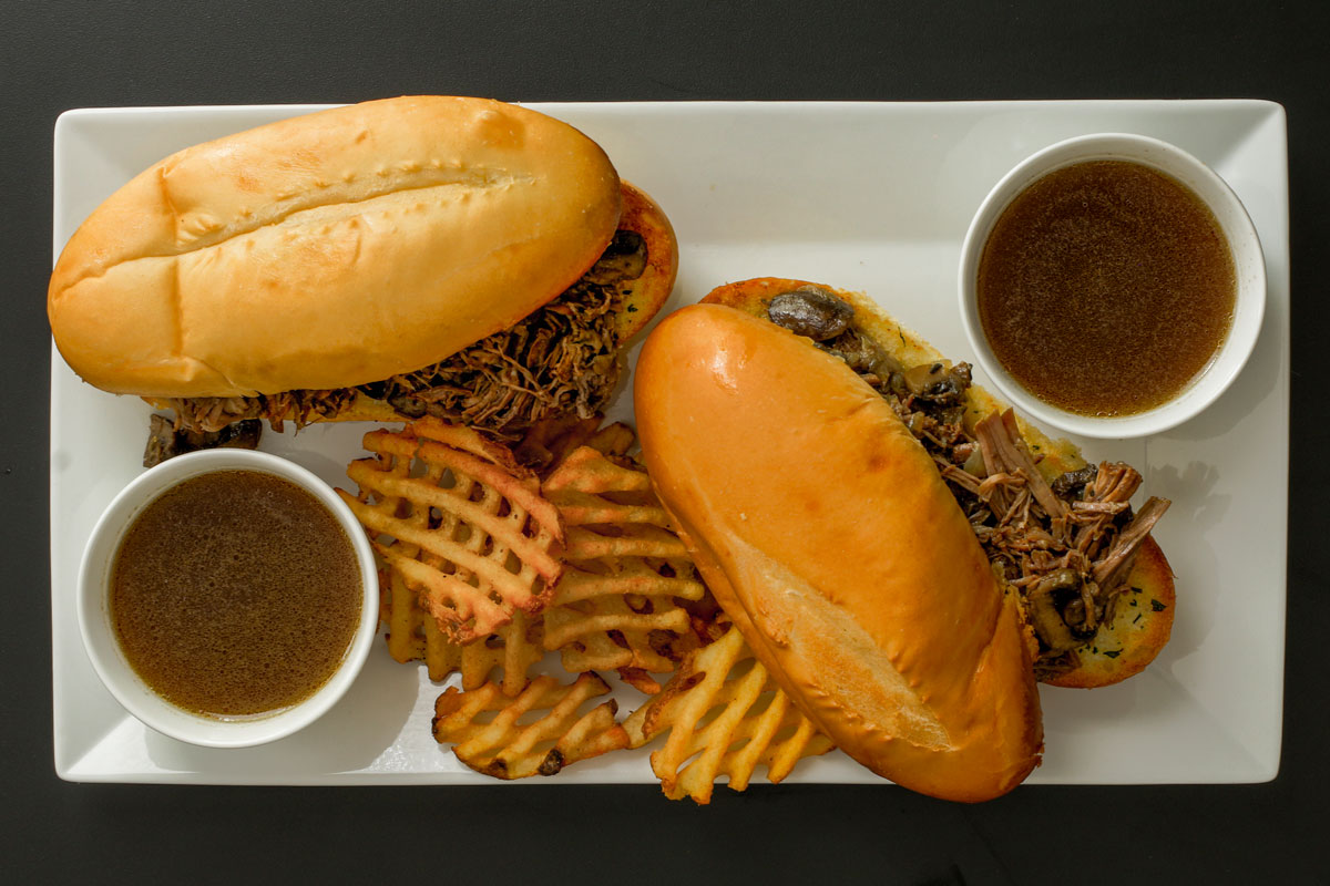 platter of french dip sandwiches with two cups of jus and waffle fries.
