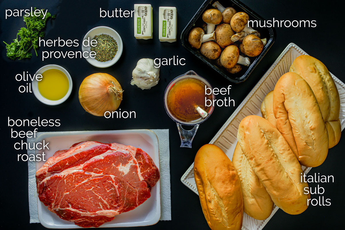 ingredients for french dip laid out on a black table.