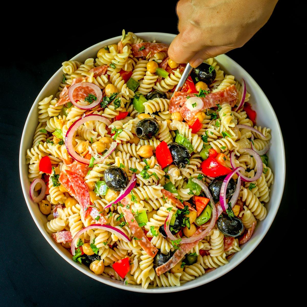 stirring a large bowl of antipasto pasta salad in a large white bowl.