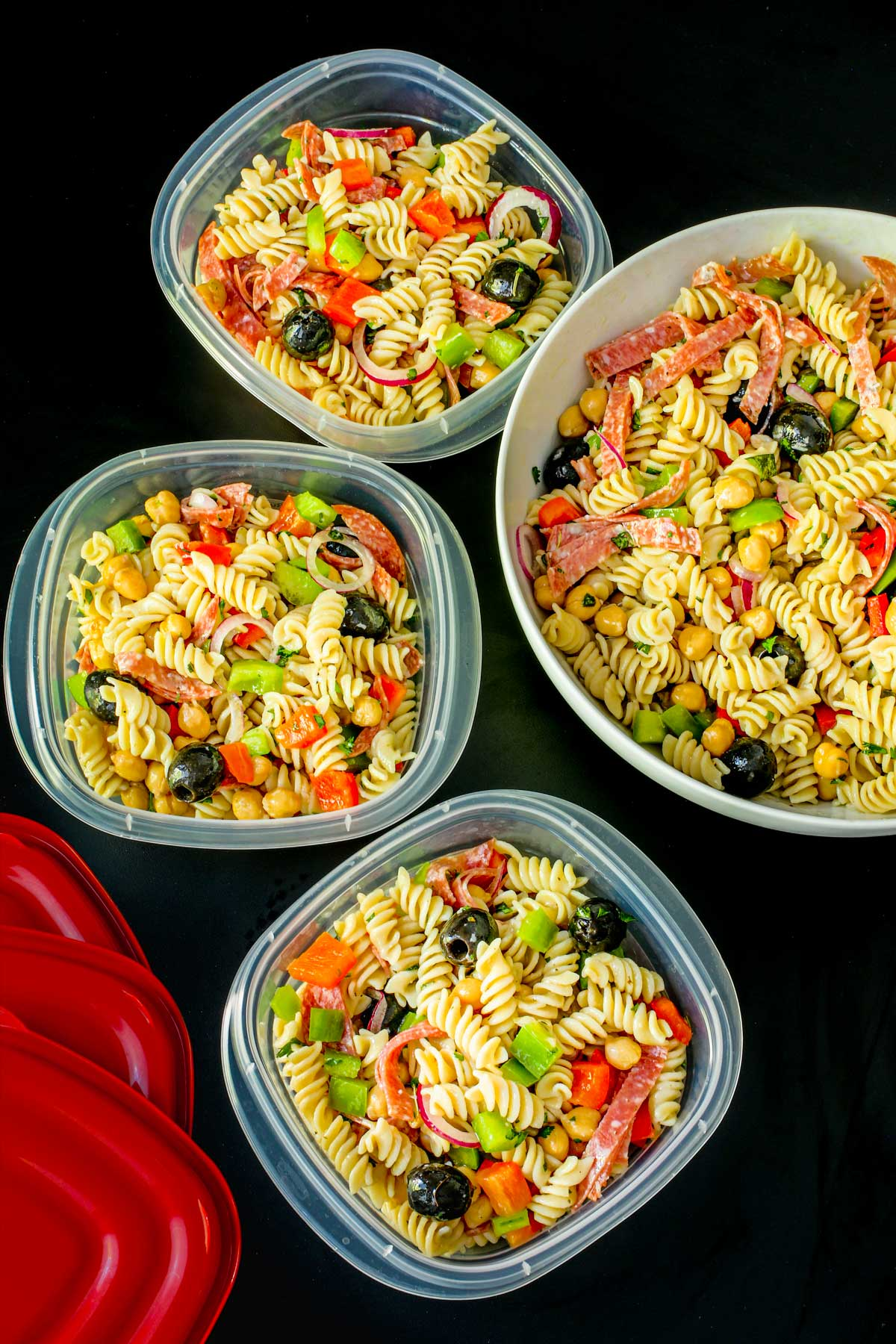 large bowl of pasta salad next to filled meal prep boxes with red lids on black table top.