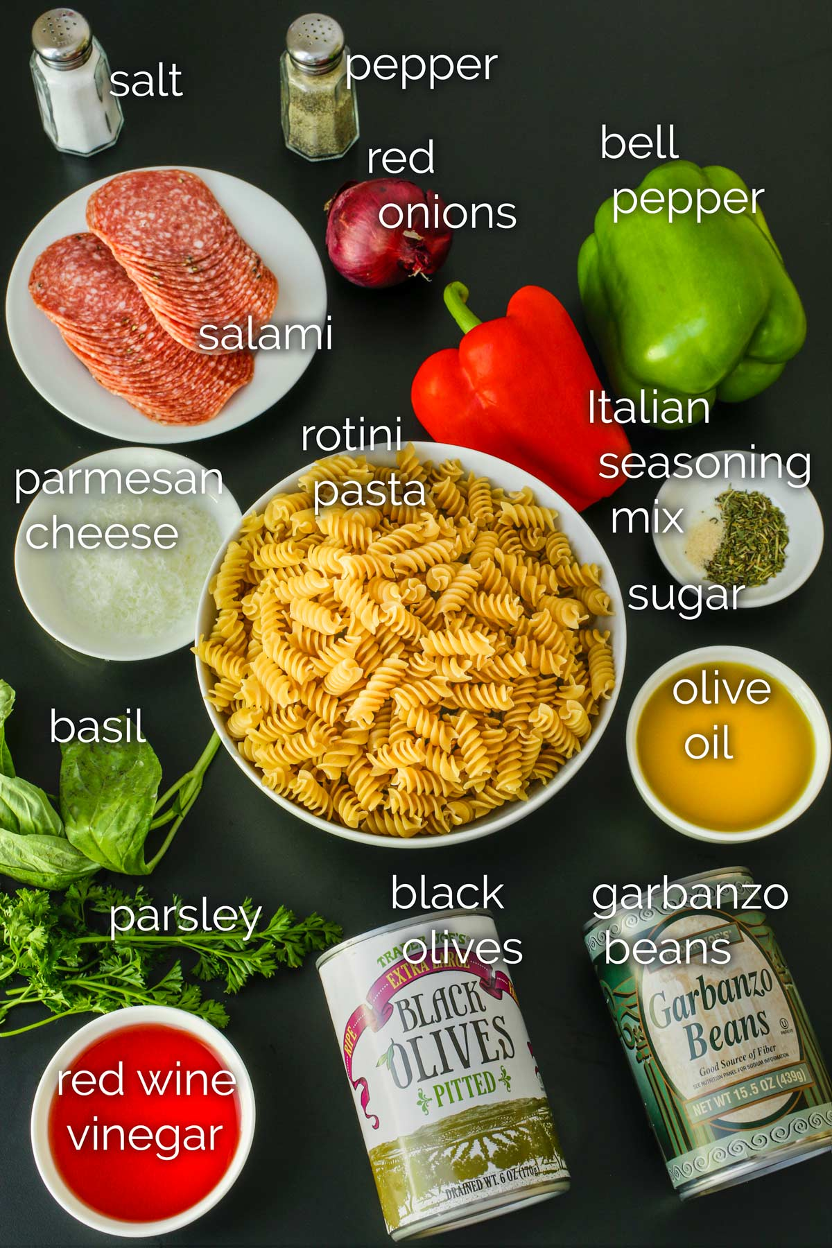 ingredients for antipasto pasta salad laid out on a black table.