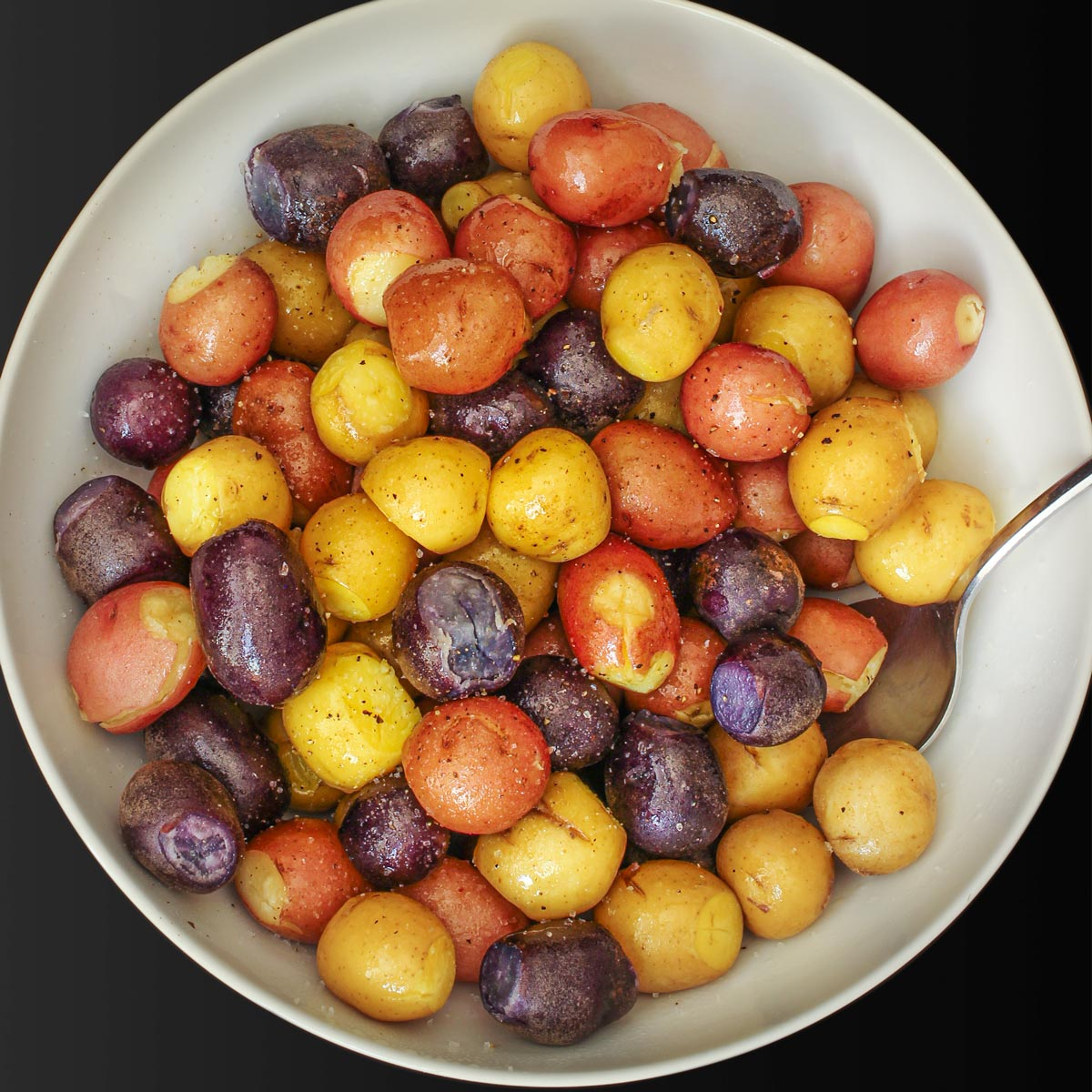 tri-color potatoes cooked and seasoned in a large white bowl.