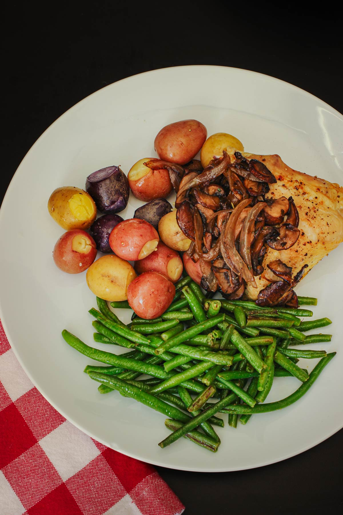 white dinner plate with green beans, potatoes, chicken, and sautéed mushrooms and onions.