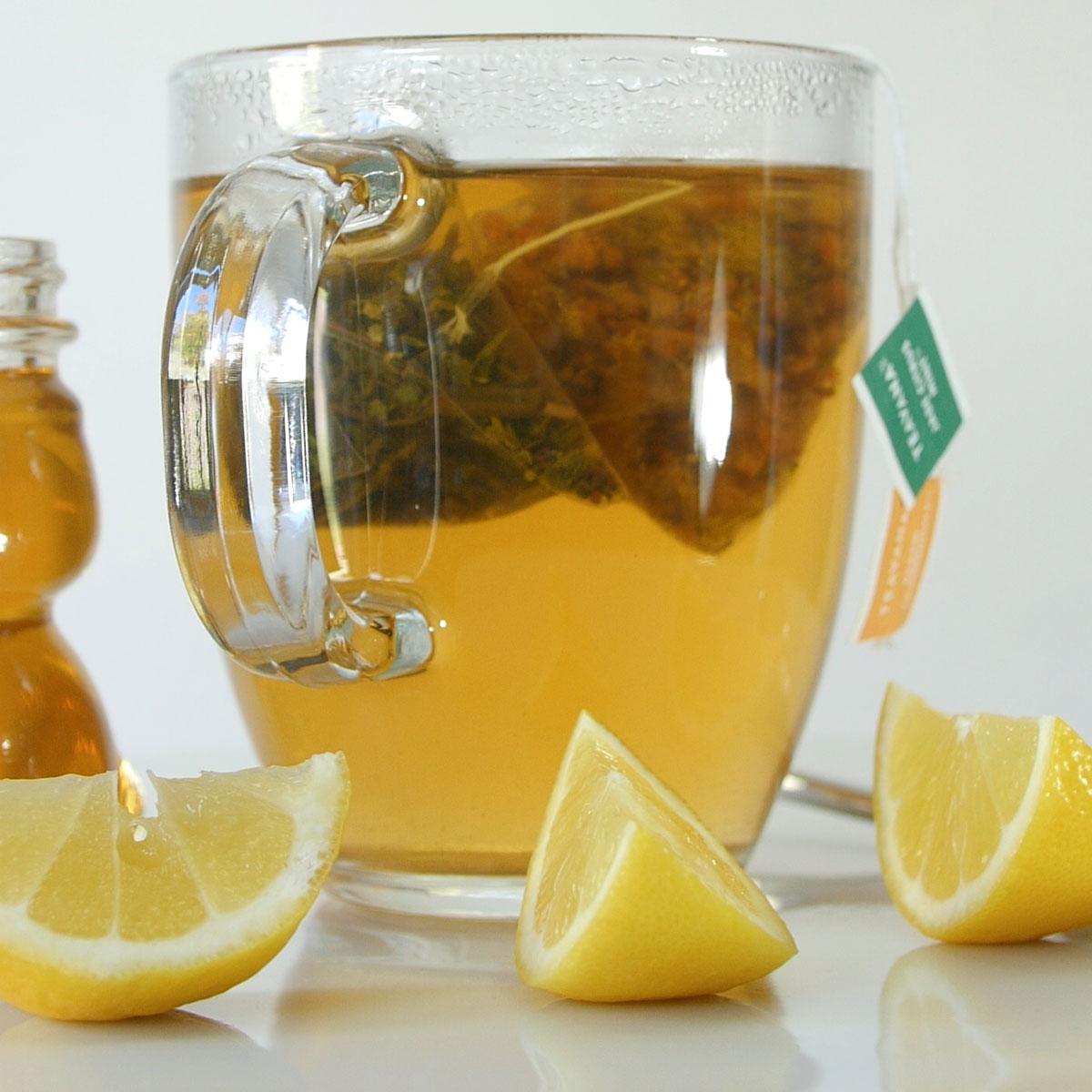 glass mug of tea next to sliced lemons and small honey bear jar.