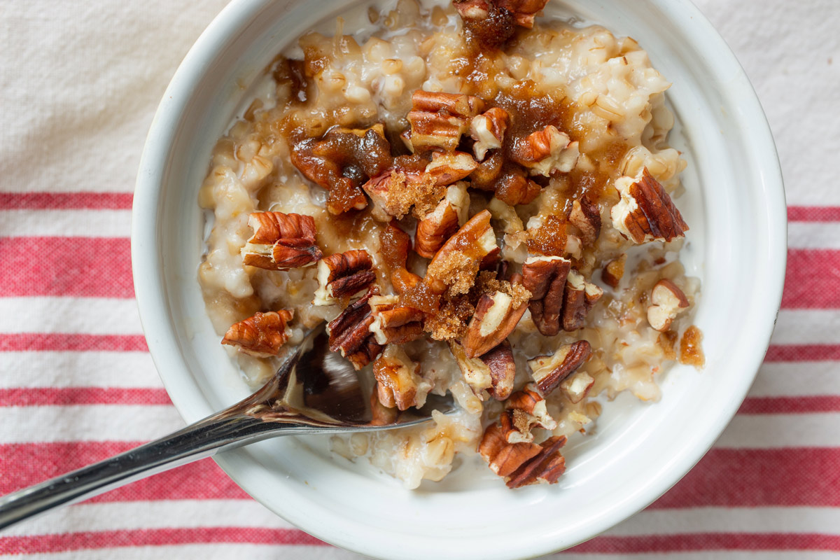 bowl of steel cut oats topped with nuts and brown sugar.