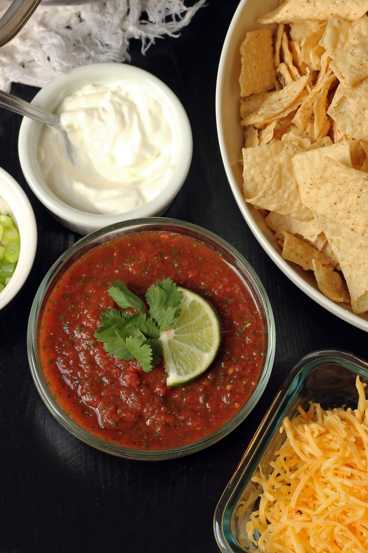 bowl of salsa on table surrounded by chips, cheese, and other taco toppings.
