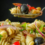 sideview of spoonful of antipasto pasta salad over bowl of salad.