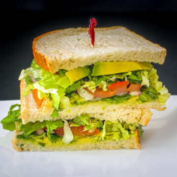 two halves of vegan sandwich with avocado stacked on a plate with a red toothpick in the top half.