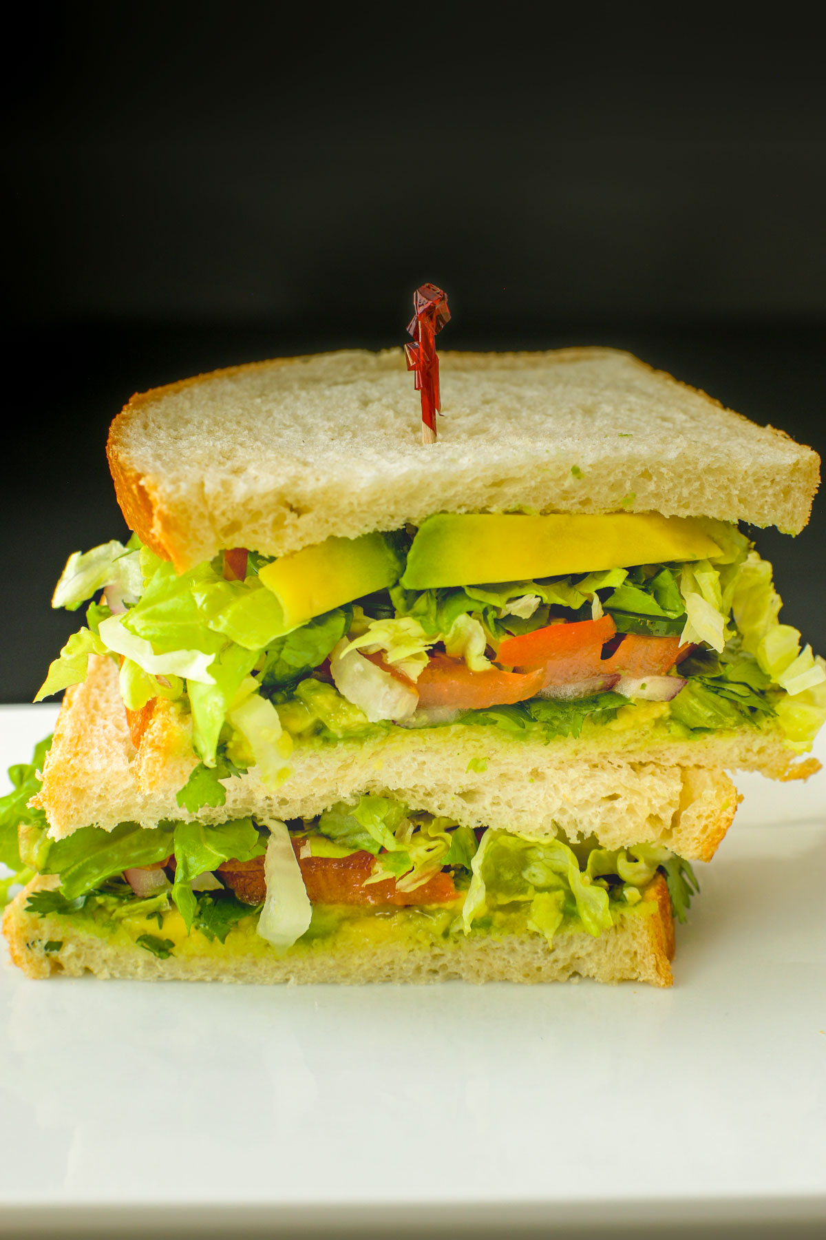 vegan sandwich with avocado cut in half and stacked on a white platter.