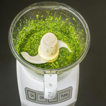 green basil sauce in bowl of food processor fitted with a metal blade.