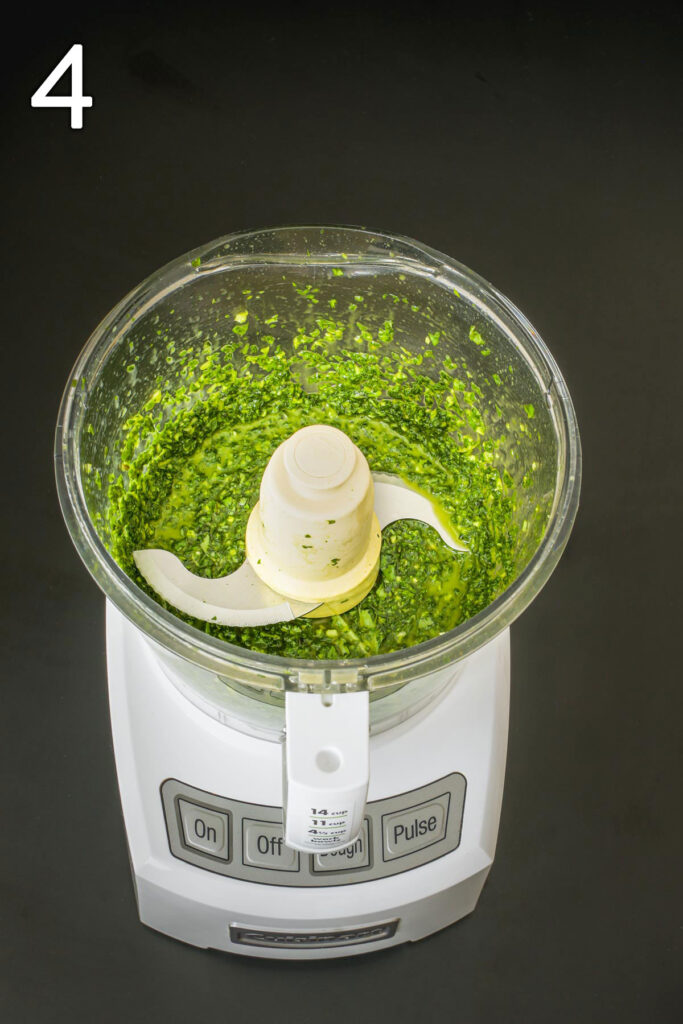 the completed basil sauce in the food processor bowl.