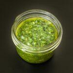 rustic basil sauce in small mason jar on a black table.