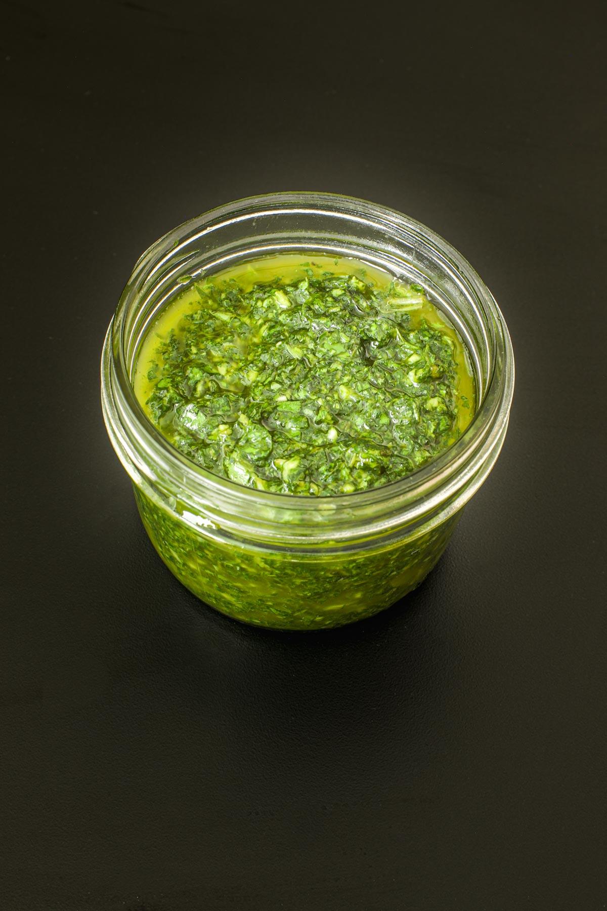 basil sauce in a 1-cup mason jar on a black table.