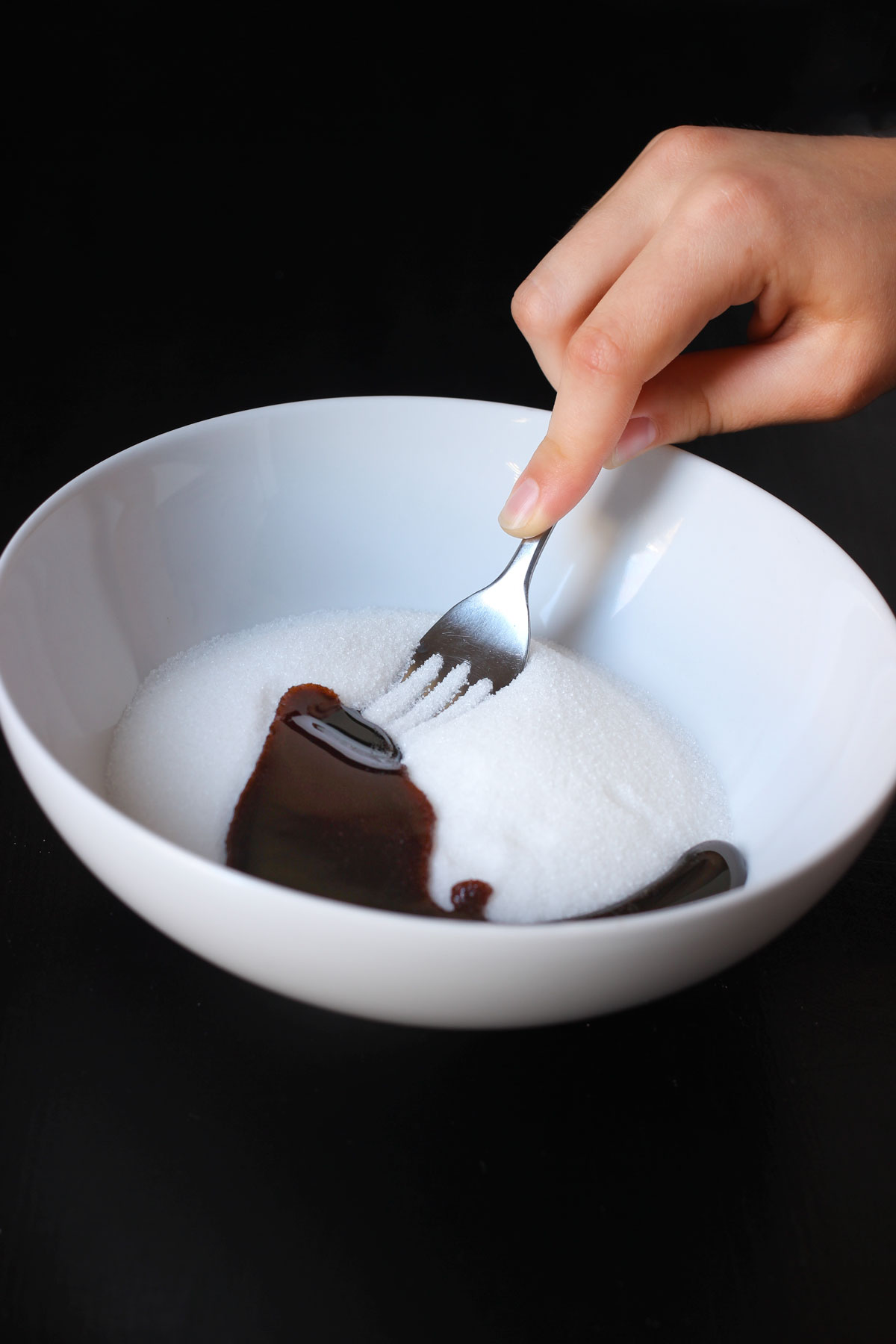 pressing a fork into the mixture to combine them.