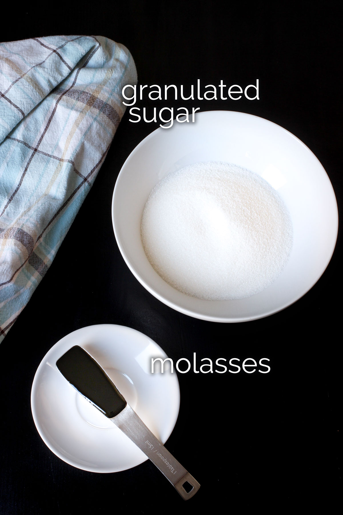 bowl of white sugar next to spoonful of molasses on table top with plaid kitchen towel.