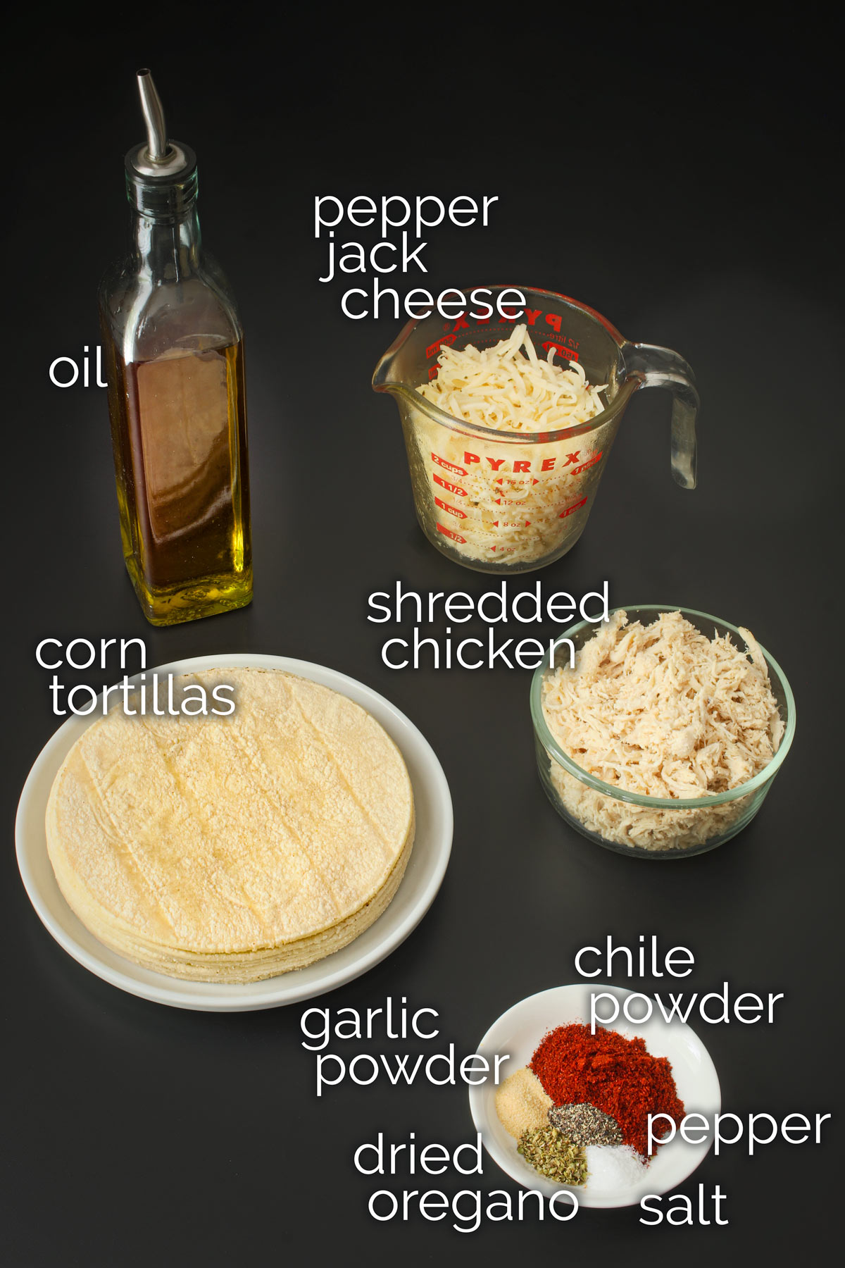 ingredients for chicken flautas laid out on a black table top.