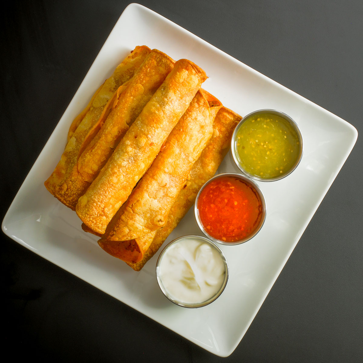 stack of chicken flautas on a square white platter with metal sauce cups with three different colored sauces.