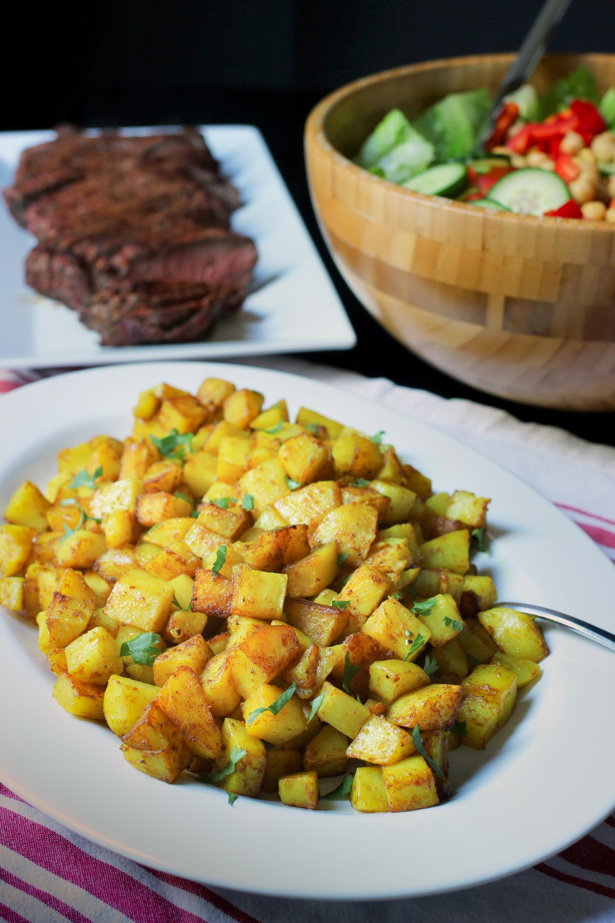 oval platter of curried potatoes on dinner table with a platter of grilled meat and a salad bowl