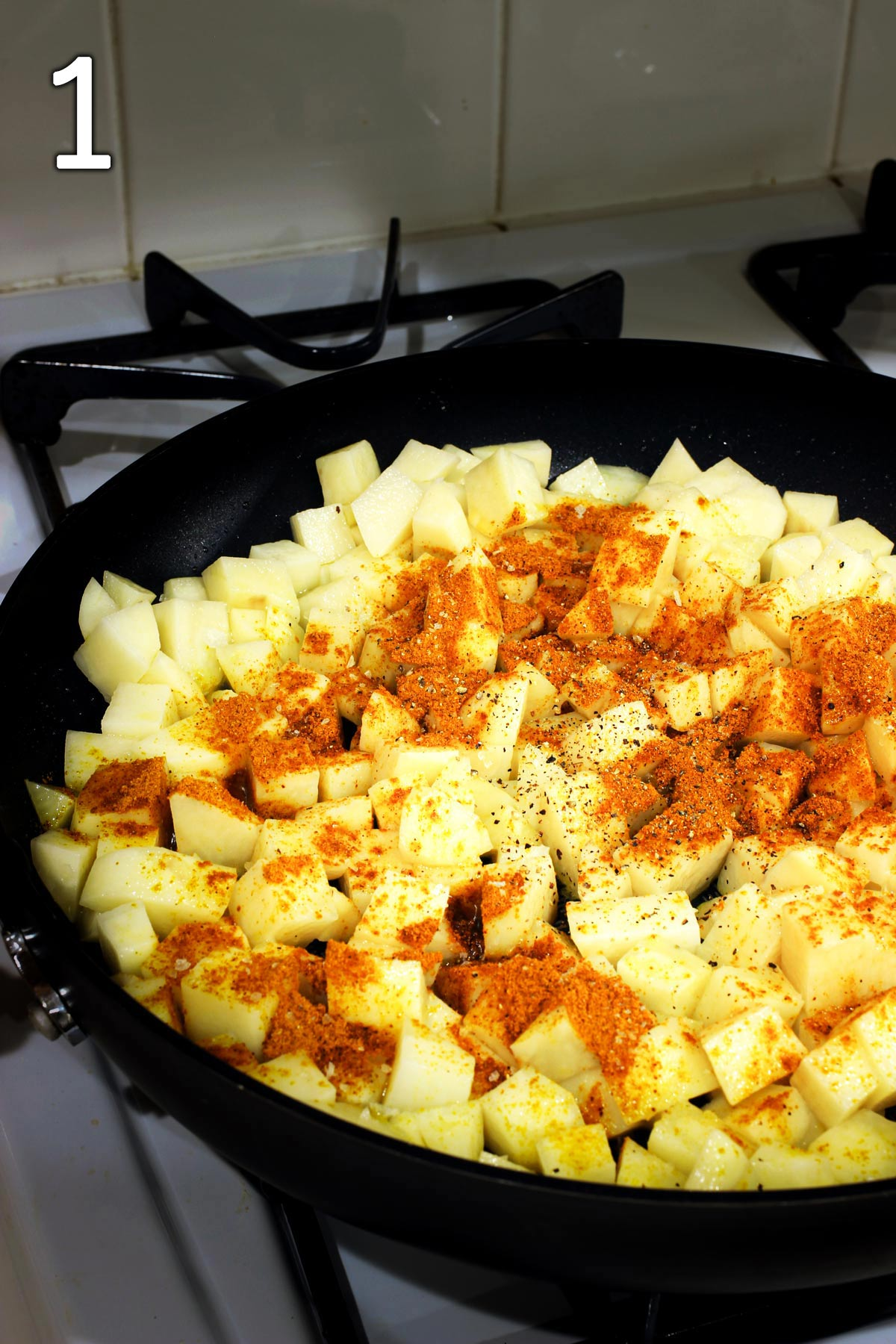 potatoes in skillet with spices.