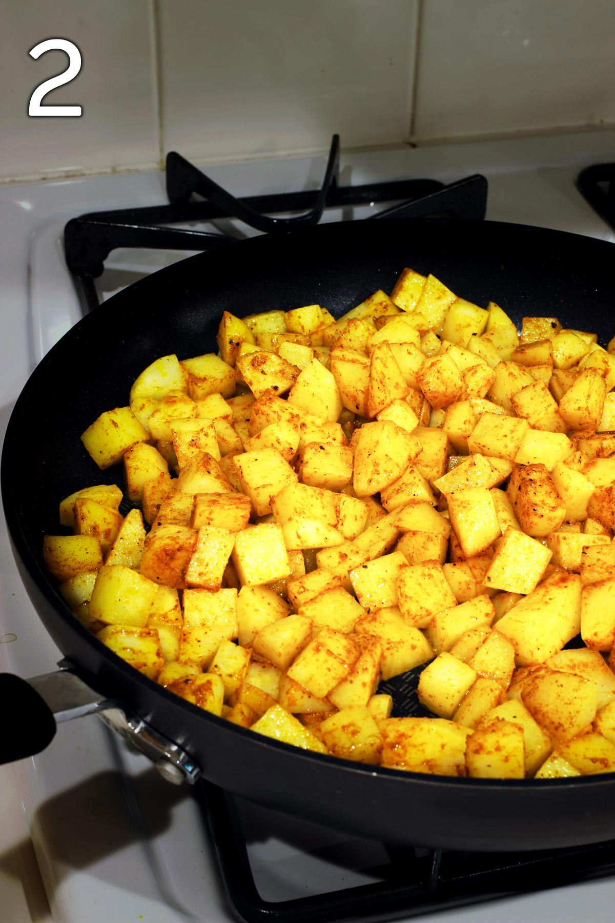 potatoes tossed in oil and spices in skillet.
