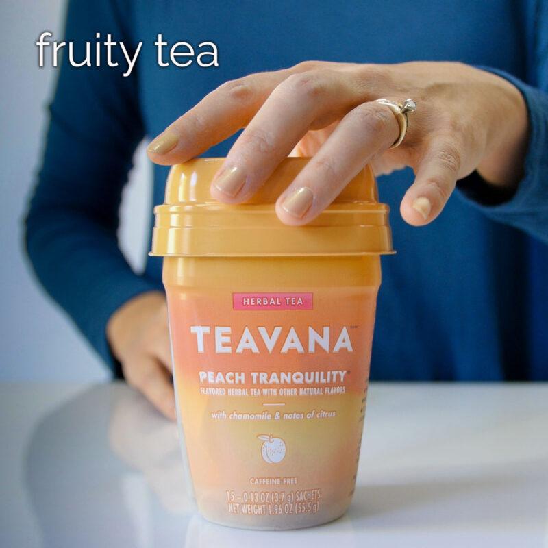 woman's hand on carton of teavana peach tranquility tea.