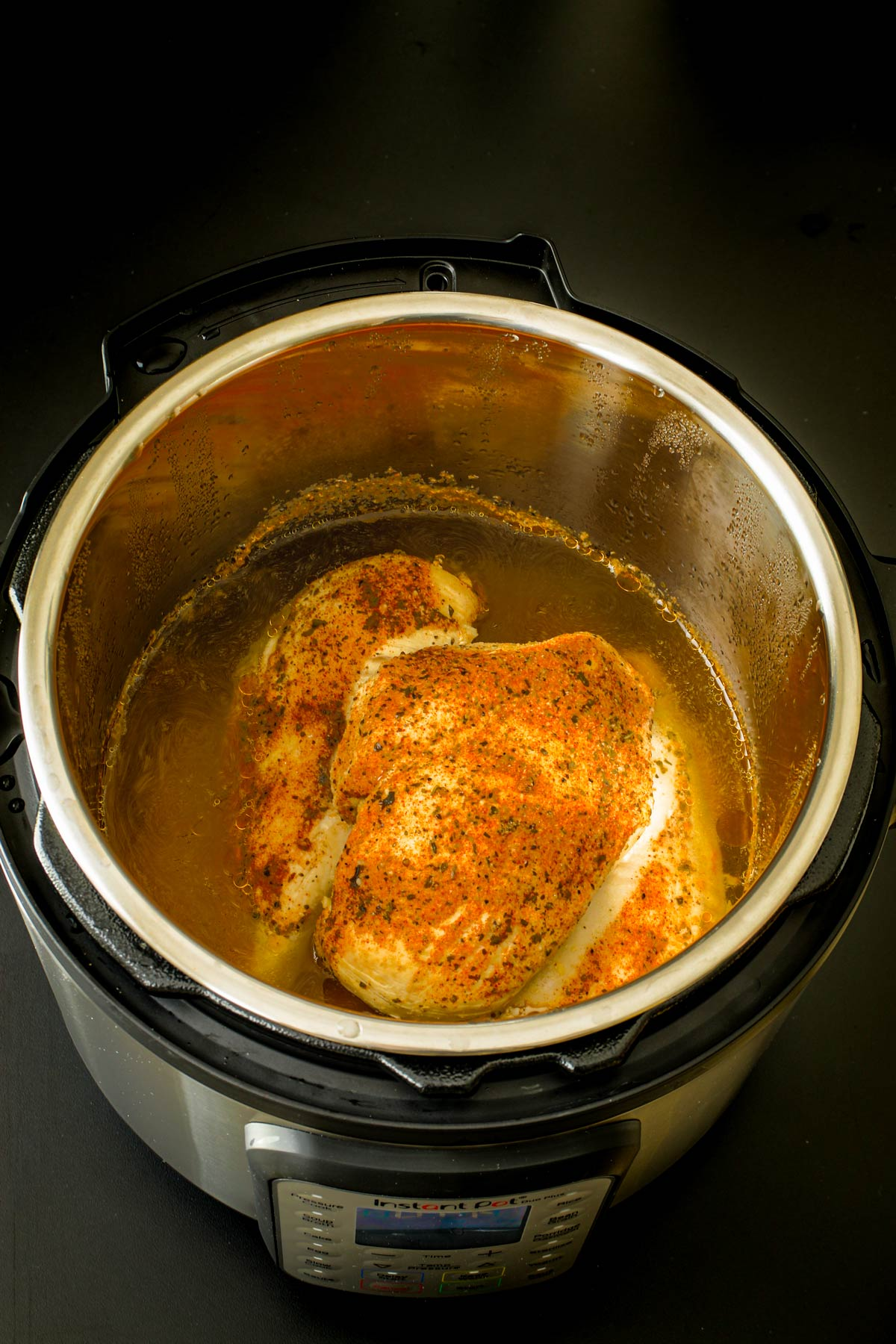 cooked chicken in broth in pressure cooker.
