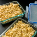 glass storage containers filled with shredded chicken next to storage lids.