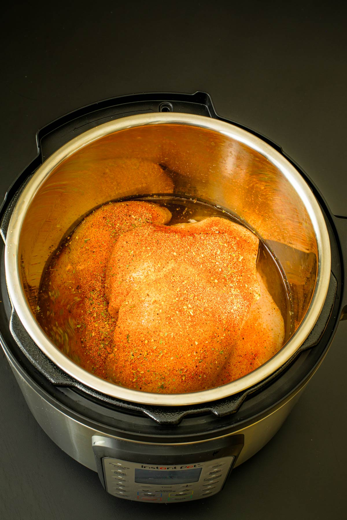 seasoned chicken and water in pot of pressure cooker.