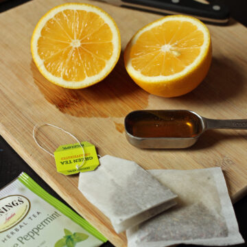 cut lemon on board next to spoon of honey and tea bags.