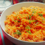 white bowl of mexican rice topped with chopped cilantro.