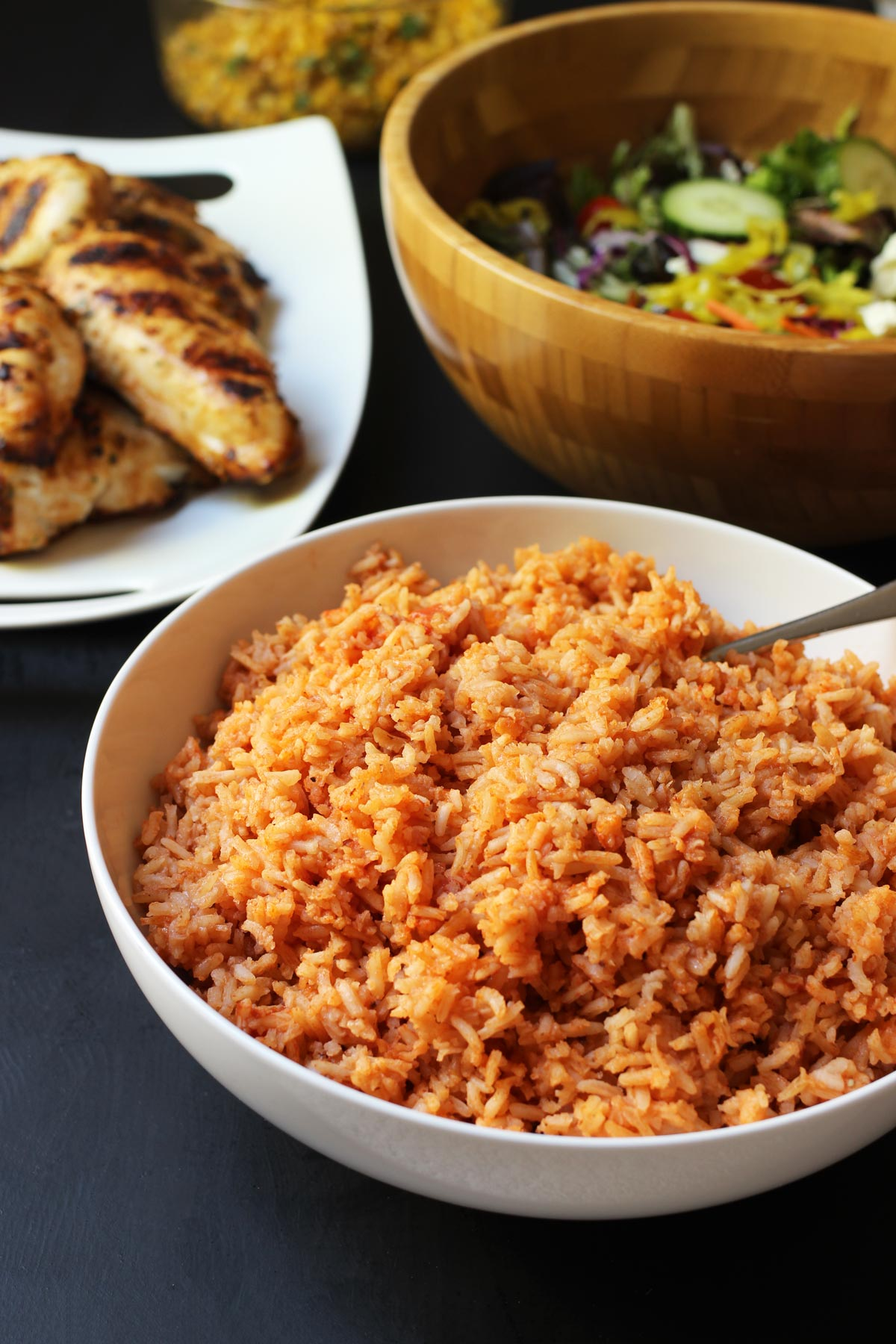 bowl of Mexican rice on dinner table with salad and chicken.