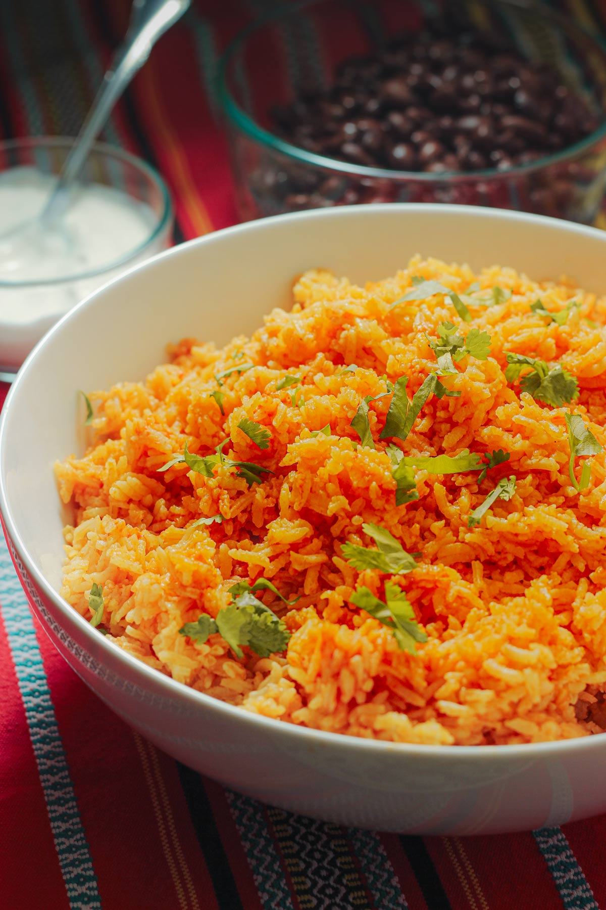 Mexican rice in large white bowl on dinner table.