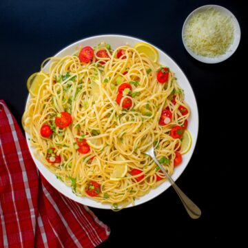 pasta with lemon and tomatoes in large platter next to red cloth and bowl of cheese.