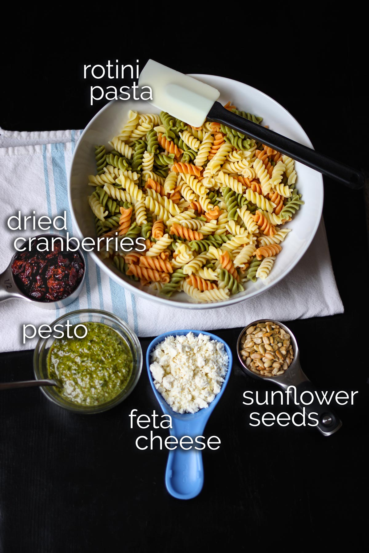 ingredients for pesto pasta salad laid out on black table top.