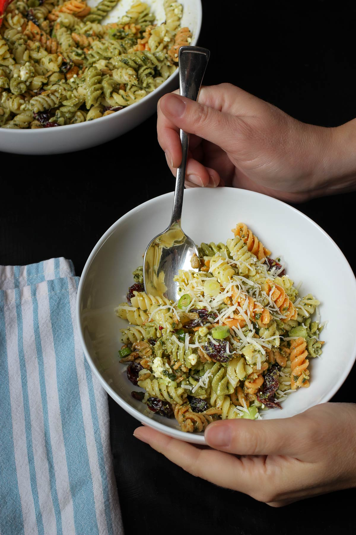 holding spoon in small bowl of pesto pasta salad.